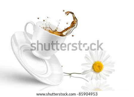 Splash of tea in the falling cup with flower isolated on white - stock photo