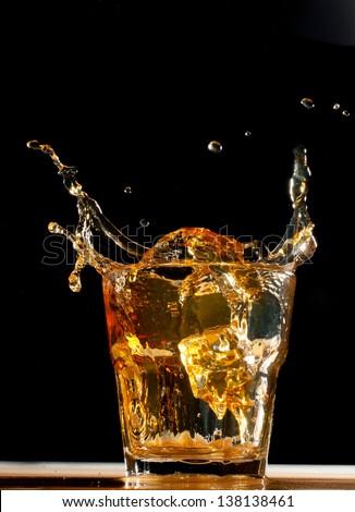 splash of whiskey in glass on black - stock photo