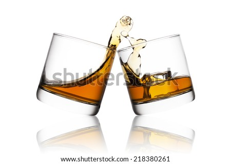 Splash of whisky in two glasses isolated on white background - stock photo