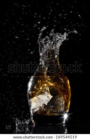 Splash water like whiskey in the glass on dark background - stock photo