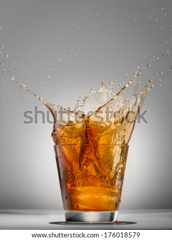 Splash water like whiskey in the glass on grey background - stock photo