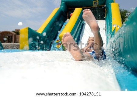 Splash! Young boy sliding down an inflatable water slide feet first while splashing water. - stock photo
