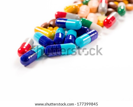 Splashed pills on white background,selective focus on the front blue pill