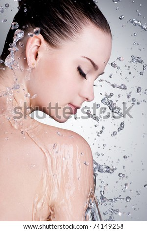 Splashes and drops of water around the female face with clean skin - vertical - stock photo