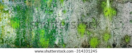 Splashes and spots of green paint on a rough wall - stock photo