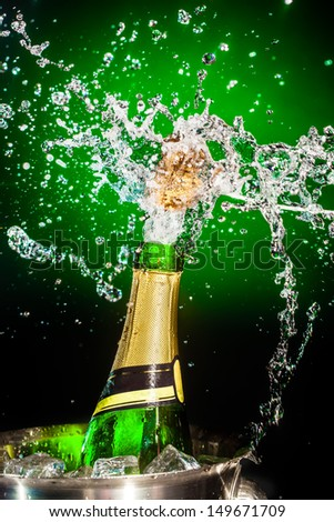 Splashing champagne on a green background - stock photo