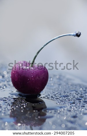 Splashing cherry, reflection surface, minimalism