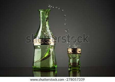 Splashing drink vodka on grey background - stock photo
