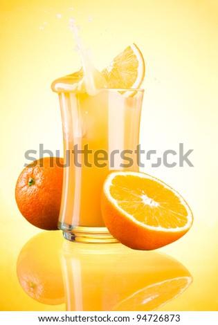 Splashing Fresh Orange Juice on yellow background - stock photo