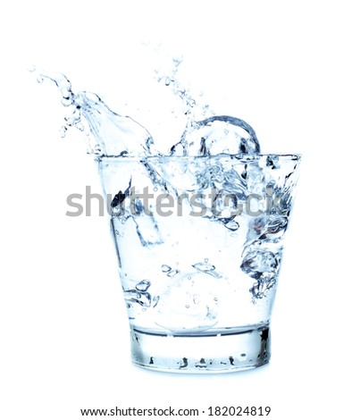 Splashing of water with ice in glass on white background. - stock photo