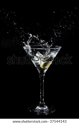 Splashing olive into a martini glass - stock photo
