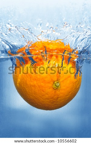Splashing orange into a water - stock photo