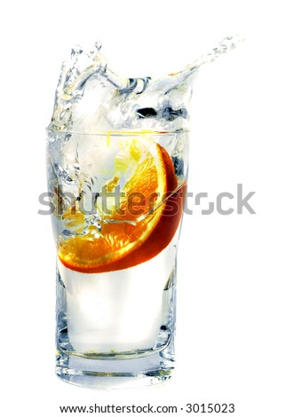 splashing orange into a water glass