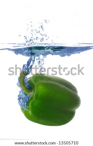 splashing pepper into a water - stock photo