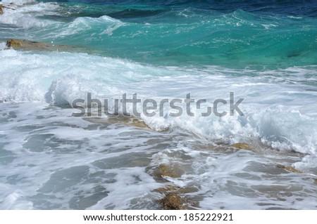 Splashing sea waves near a rocky beach - stock photo