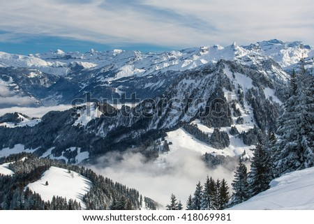 Splendid winter alpine scenery with high mountains and trees covered with snow, clouds hanging low in the valley - stock photo