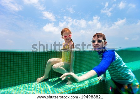 Split above and underwater photo of adorable kids having fun in swimming pool on summer vacation - stock photo