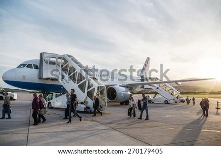 SPLIT, CROATIA - MARCH 6, 2015: Passengers exiting Croatia Airlines' Airbus A320 parked on a runway of Split Airport. This airport is a Europe's main connection to Adriatic coast. - stock photo