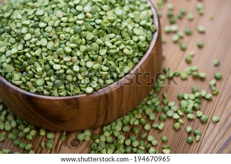 Split dried peas in a wooden bowl, close-up, studio shot - stock photo