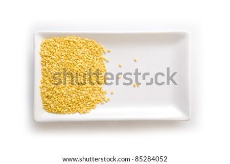 Split dried peas on a white plate - stock photo