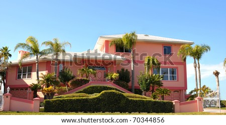 Split level ranch, mansion with dual stairs leading to double door entryway. It incorporates a dual garage on each side of the home. Manicured hedges with gated driveway elicits feeling of privacy. - stock photo