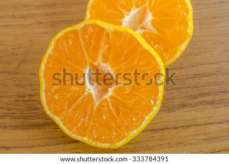 Split oranges on wooden table - stock photo