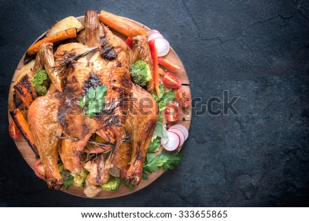 Split roasted turkey and vegetables on the dark background,selective focus and blank space  - stock photo