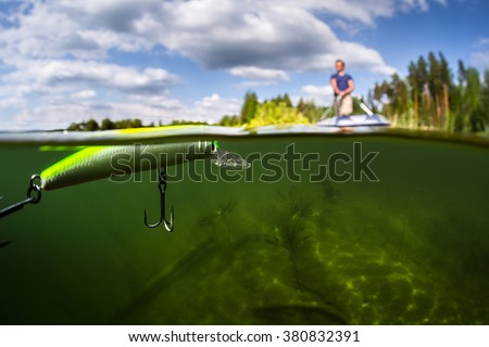 Split shot of the man fishing from the boat on the lake. Underwater view of the lake. Focus on the bait - stock photo