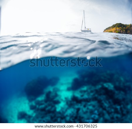 Split shot with underwater view of the coral reef and sailing boat on the surface - stock photo