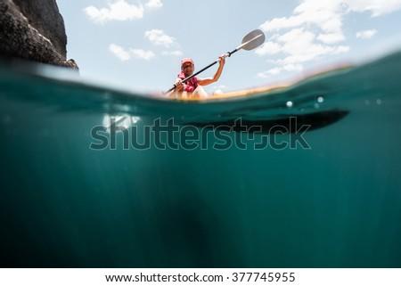 Split shot with underwater view of the mature man paddling the sea kayak at sunny day - stock photo