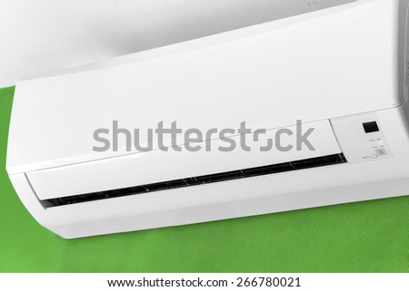 Split-system air conditioner on green wall  - stock photo