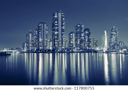 split toned image of Tokyo skyline in modern Tsukishima district with scenic water reflection in Sumida river - stock photo