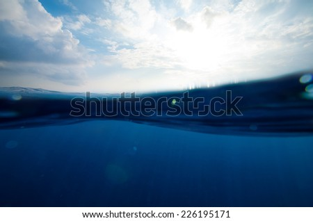 split underwater and sky background with sunbeams - stock photo