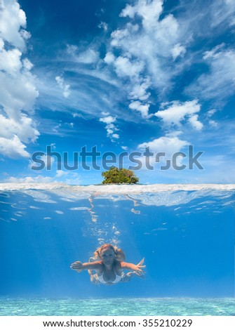Split Underwater portrait of a woman snorkeling in tropical sea - stock photo