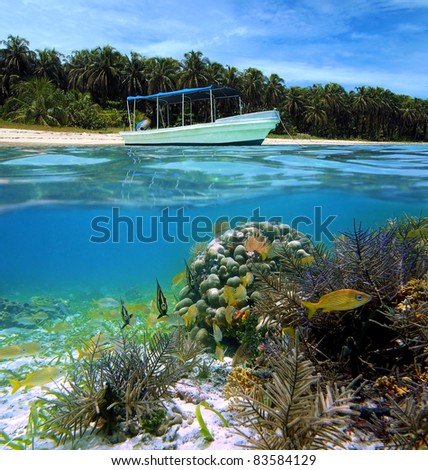 Split view of tropical beach with a boat anchored and underwater corals with tropical fish, Caribbean sea, Bocas del Toro,  Zapatillas islands, Panama - stock photo