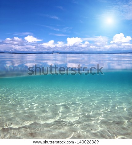 Split view over and under the water in the Caribbean sea with clouds reflected on surface and a sandy sea floor - stock photo