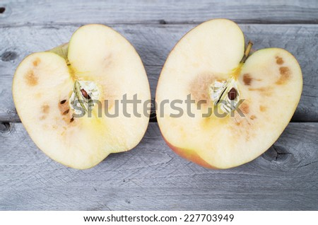 Spoiled apple cut in two half on wooden background - stock photo