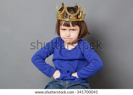 spoiled kid concept - sulking preschool child with golden crown on head putting hands on hips for confident mollycoddled little king or queen metaphor,studio shot - stock photo