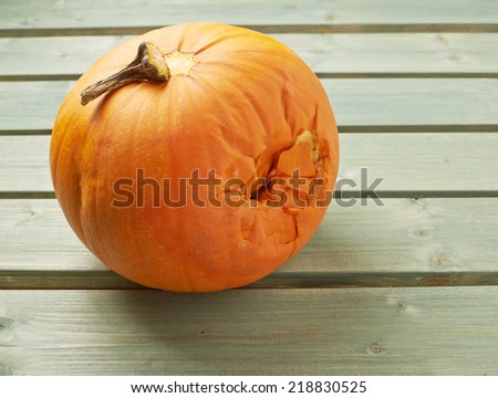 Spoiled orange pumpkin over the background made of green painted wooden boards - stock photo