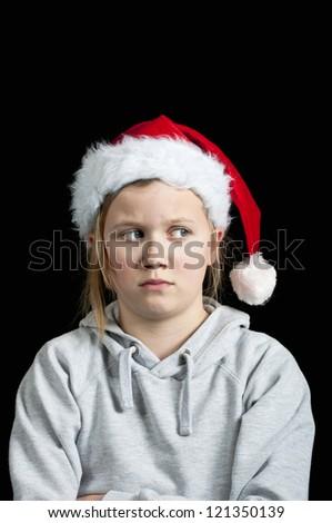 Spoilt child wearing a santa hat - stock photo