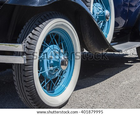 Spoked wheels painted aqua blue on a vintage automobile. - stock photo