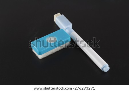 Sponge and pencil on blackboard - stock photo