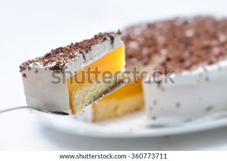 sponge cake with cream and yellow gelatin on metal spoon, tart on white plate, patisserie, photography for shop, birthday cake - stock photo