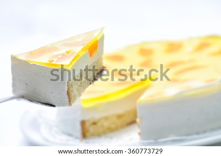 sponge cake with cream, fruit and yellow gelatin on metal spoon, tart on white plate, patisserie, photography for shop, birthday cake - stock photo