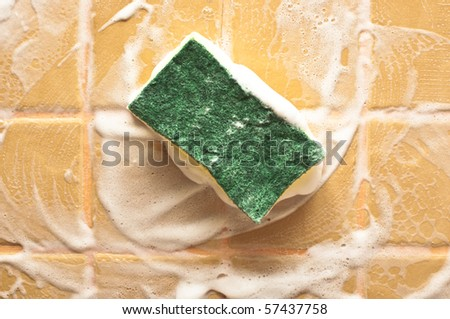 sponge for cleaning with foam on wall - stock photo