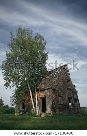 Spooky abandoned rural house in the field. - stock photo