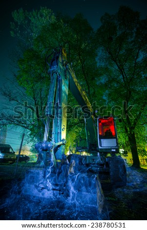 Spooky abstract excavator at night - stock photo