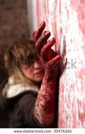 Spooky bloody hand is trying to catch a wall - stock photo