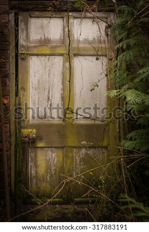Spooky doorway to a haunted house or nightmare overgrown and forgotten - stock photo