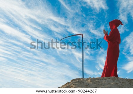 Spooky figure in red cloack with scythe - stock photo